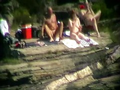 Nudist couple in the sun fucks as a voyeur films from across the way